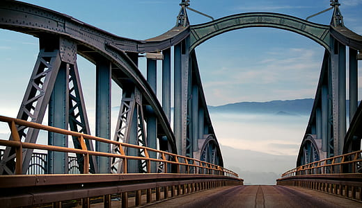 gray and brown suspension bridge under blue sky