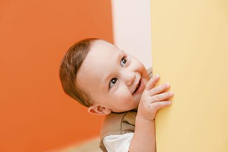 baby touching yellow wall