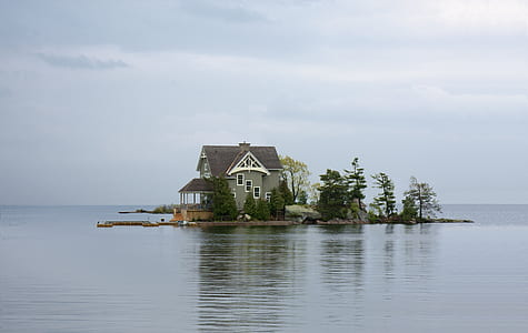 white and brown wooden house in front of lake photography