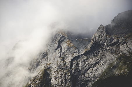 photo of rock mountain covered by fogs