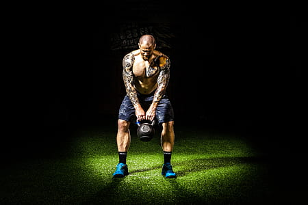 man with tattoos carrying black kettle bell
