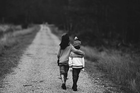 two children walking on road