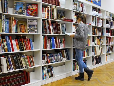 woman reading book near shelves
