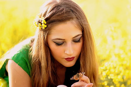 closeup photo of woman wearing green sleeveless top with butterfly on her hand