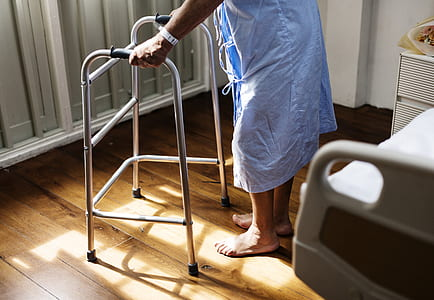 person walks with gray metal folding walker near closed door during daytime