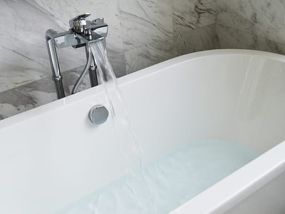white ceramic bath tub with stainless steel faucet during daytime