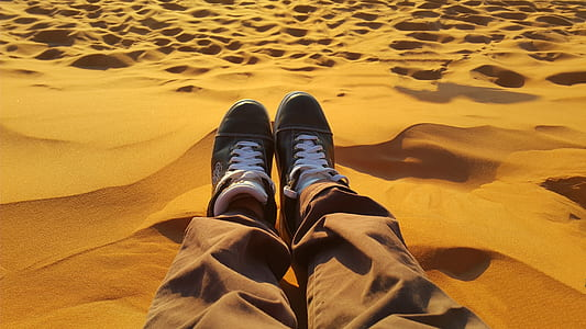 person sitting on sand dunes