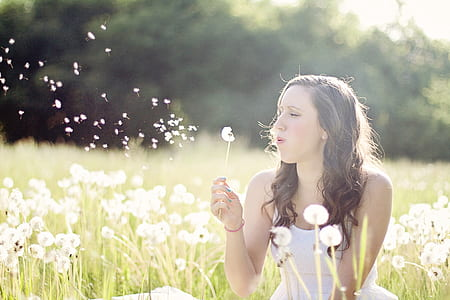 woman wearing white top on dandelion grass field during daytime
