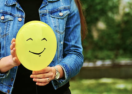 woman in blue denim jacket holding yellow plastic balloon