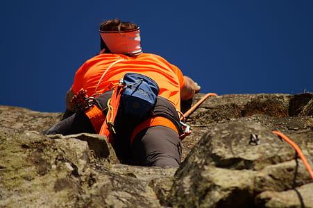 Person in Orange Shirt Climbing Rock during Daytime