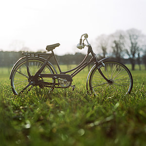 shallow focus photography of brown beach cruiser bicycle on grass field