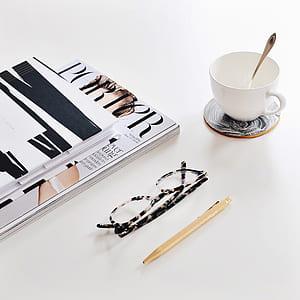 black and white framed eyeglasses near mug and books