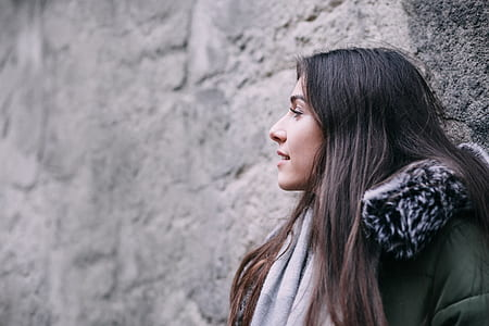 woman wearing green and black coat looking side view