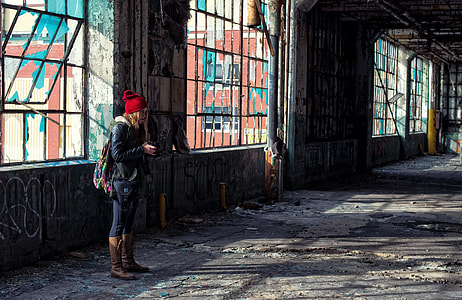 woman wearing red knit cap inside abandoned building near window