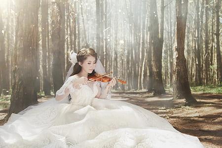 woman in white wedding dress playing violin