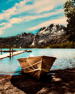 brown canoe boat against body of water and mountain