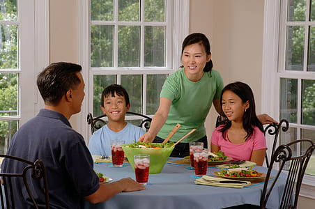 woman standing beside two kids near man sitting on dining table