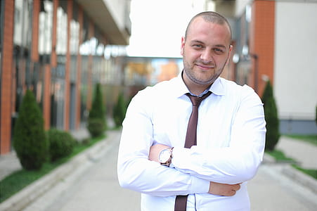 man in white dress shirt with brown silk necktie standing near building