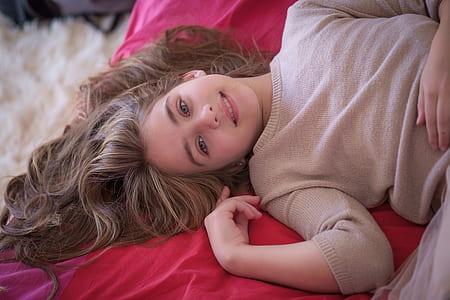 girl in red dress lying on red blanket