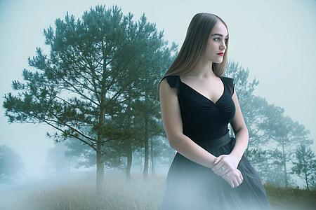 woman in black scoop-neck dress near forest