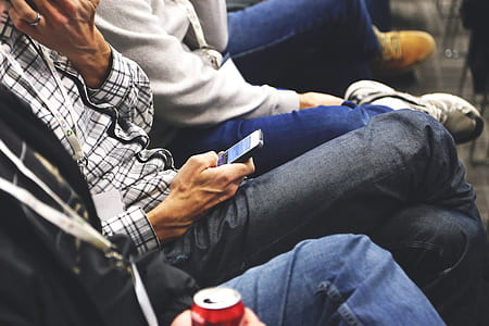 person holding smartphone sitting on chair