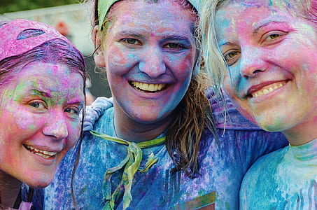 three women with assorted-color on their faces