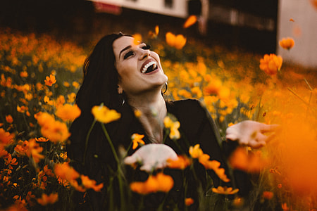 Laughing woman in flowers with smile