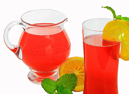 red juice in pitcher and glass with slice of lemon