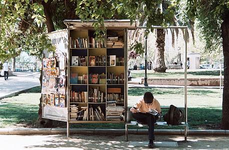 man in orange shirt sitting on bench beside bookshelf