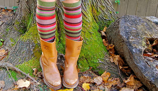 person wearing brown leather cowboy boots standing near brown tree during daytime