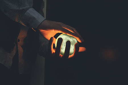 Closeup shot of a man's hands holding a glowing orb