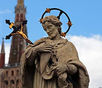 statue of man holding crucifix