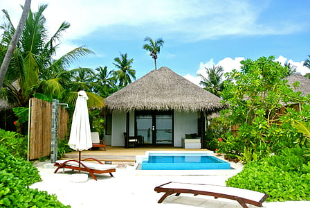 landscape photo of two house behind swimming pool with two loungers