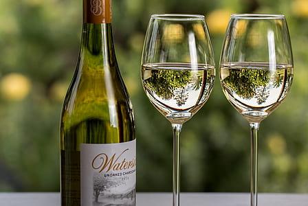 two wine glasses beside wine bottle