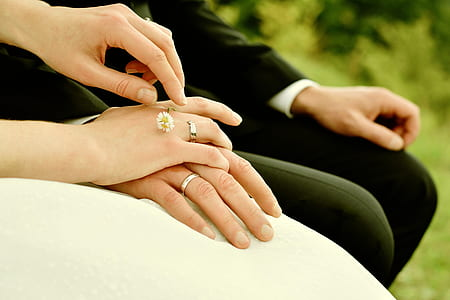 bride and groom sitting on chair holding hands