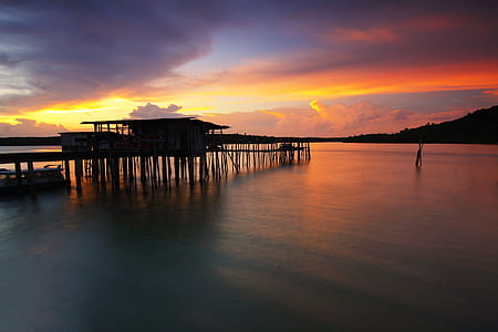Silhouette of Wooden House Above Sea during Sunset