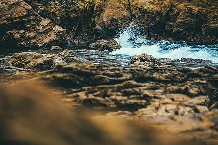 brown rock between water