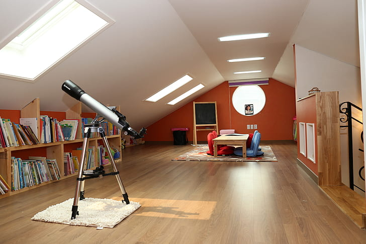 gray telescope near brown wooden book shelf
