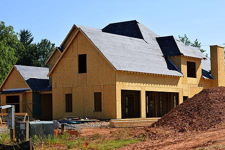 brown house beside soil under clear skies