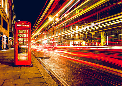 red telephone booth on concrete ground near buildings at nighttime
