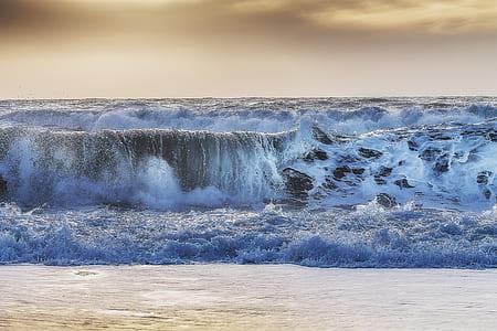 ocean waves taken under white clouds during daytime