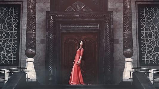 woman wearing red dress standing in-front of door