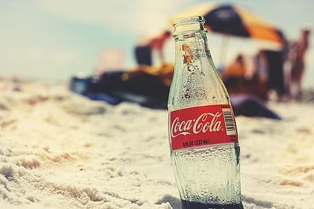 Coca-Cola glass bottle on seashore