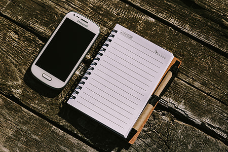 White smartphone with various items on a wooden background