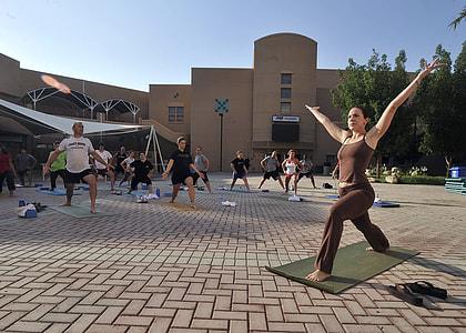 people performing yoga under blue sky