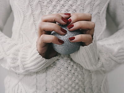 person wearing white sweater holding glitter ball