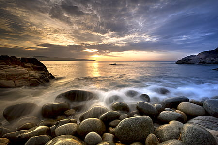 gray stones beside sea at daytime