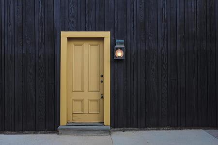 brown wooden 4-panel door and black painted wall