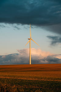 white wind turbine on the brown grass field