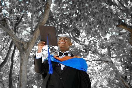 man in black academic dress under trees